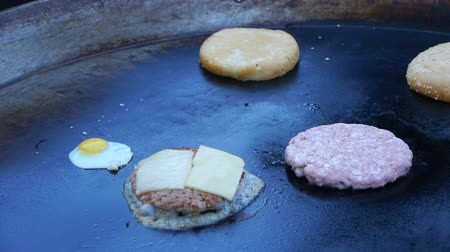 karkówka : Cook uses a blow torch to melt cheese on a meat cutlet. Chef melts cheese on a burger using a blow torch.