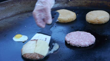 kıyma : Cook uses a blow torch to melt cheese on a meat cutlet. Chef melts cheese on a burger using a blow torch.