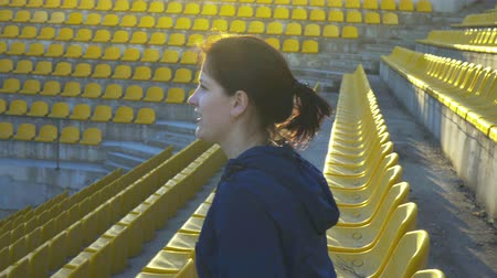 One girl sits in the grandstand of the stadium, 4k Stok Video