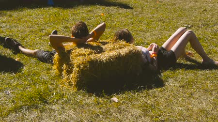 A guy and a girl are lying on the hay Stok Video