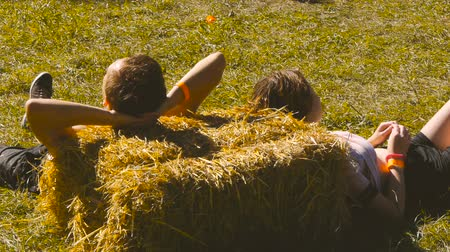A guy and a girl are lying on the hay Stock Footage