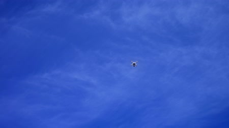Copter, drone flying in a blue sky, Quadrocopter against the blue sky with white clouds