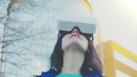 Young woman wearing VR glasses, headset, playing virtual games and watching videos outdoors against the background of a glass building Stok Video