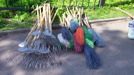 a man takes and throws a broom, Rakes and brooms for cleaning the backyard