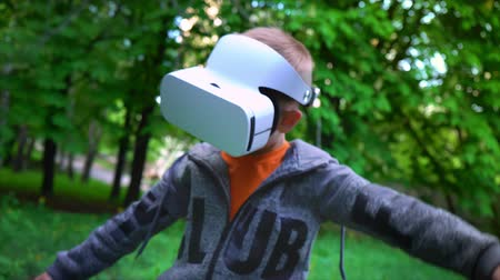 Little boy using virtual reality headset in the flight simulator in the summer park