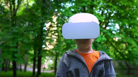 Child in VR glasses fighting off something in the summer park, child have fun experiencing 3D gadget technology
