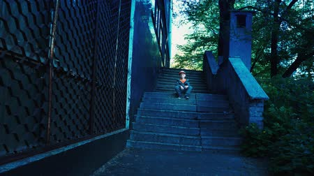 A lonely child is sitting on empty steps on the street, a 5 year old boy with a serious face posing on the camera