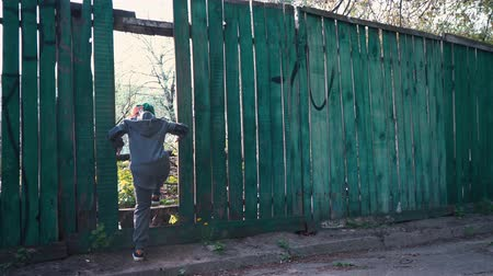 The boy runs through the gap in the old wooden fence