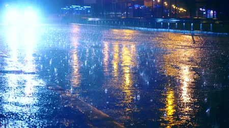 pocsolya : Cars drive into large puddles on the night road in the city, spray puddles scatter from under the wheels of the car