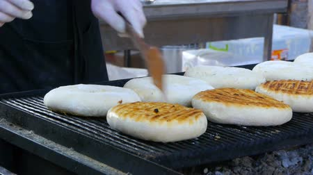 pita : Baker is turning round grain tortillas on the grill, baking bread, national bread, street food