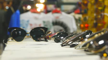 exibindo : Collection of sunglasses on the counter, Large selection of sunglasses