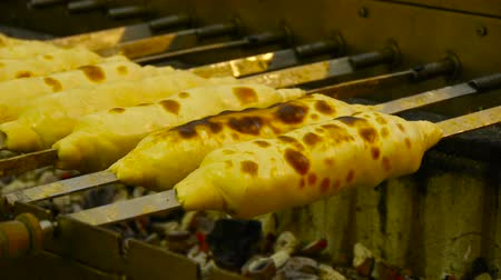 špejle : Georgian traditional dish - khachapuri, pastry with cheese rotating on a skewer fried on the grill Dostupné videozáznamy