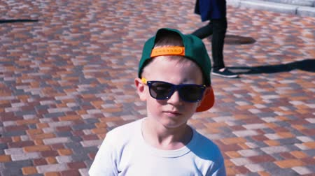 green peach : Young boy in sunglasses and a cap walking down the street, Child 6 year old kid walking, slow motion Stock Footage