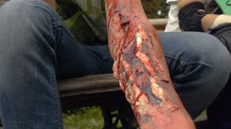 falsificação : Fake wound on the guys hand, bleeding wound on the arm of the zombie, halloween make-up Stock Footage
