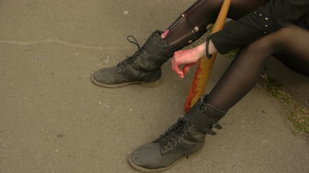 bat : An unrecognizable young girl with bloody basketball bat in her hands sits on the street and smokes Stock Footage