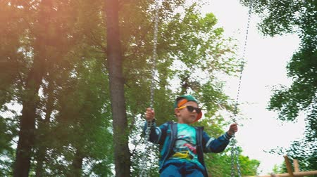 suspensão : Little boy in sunglasses and a green cap swinging on a swing, A 5-year-old child has fun on a childrens swing surrounded by green trees Stock Footage