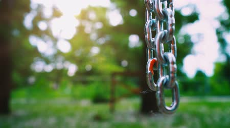 linked : A strong steel chain with large links hangs down against the background of nature