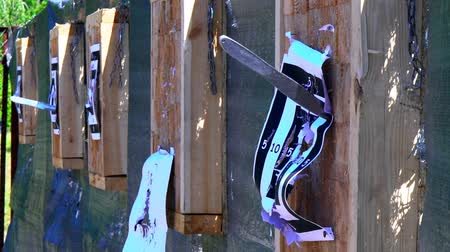 házení : Throwing knives at the target from an open-air distance, a competition for throwing knives, flying knives, sharp knives fly in a target from the wood stands, slow motion