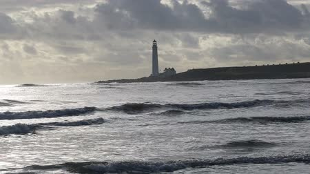 Waves and Scurdie Ness lighthouse near Montrose Scotland