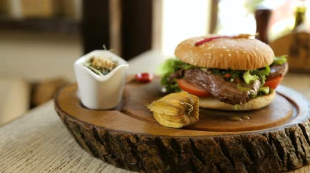 kazık : Juicy beef hamburger meal on a sesame seed bun topped with bacon and cheese and served with crisp French fries