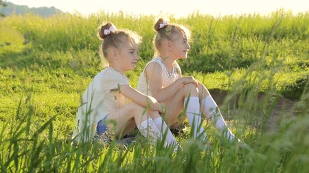 cimborák : Two little girls sitting on grass talking have fun