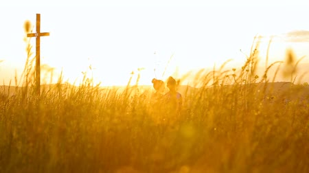 holding steady : Two sisters walking in a field during sunset holding gands
