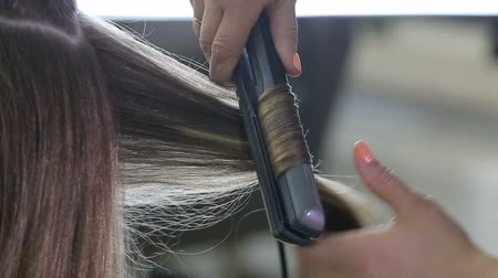 curling hair : Professional hairdresser stylist curling up teen girl hair Stock Footage