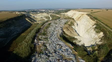 Aerial shot of garbage dump between agricultural fields. Drone fly above trush.