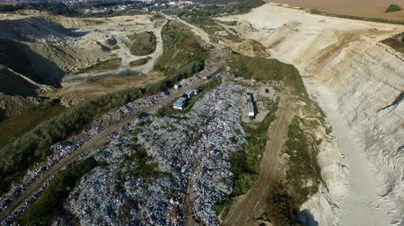 Aerial shot of vehicle bringing garbage to dump. Drone video above rubbish pile