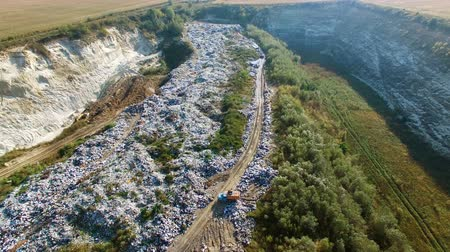 Aerial view of trash dump beetween agricultural fields. Truck unloading rubbish to pile Wideo