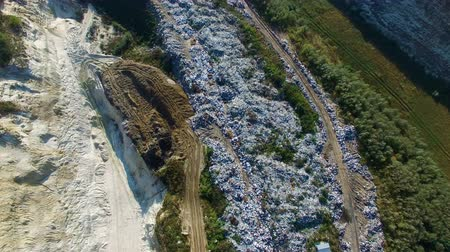 Fly about garbage dump. Excavator working on the ground. Aerial view. Wideo