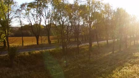 Aerial view close to young man in white helmet riding motorcycle at autumn sunset towards west!