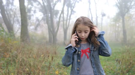 perdido : Little European girl with a long hair, blue jacket, black pants, sneakers and blue eyes. A frightened little child is walking through the foggy deserted forest and talking cell phone. Loneliness. Steady cam front medium shot.