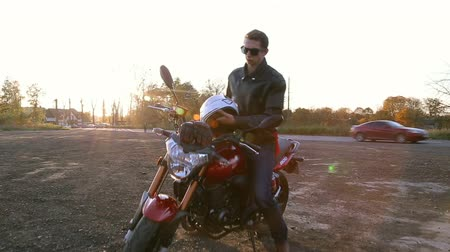 A young man in black leather jacket with white helmet goes to his motorcycle and sits on it before journey at autumn sunset. Steady cam shot.