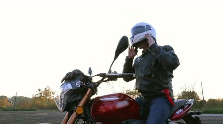 A young man in a black leather jacket sits on a motorcycle, puts on a sun glasses and puts on a white helmet. Steady cam shot. Wideo