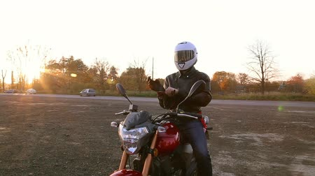 A young man in a black leather jacket and white helmet sits on a motorcycle. Steady cam shot. Wideo