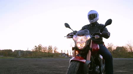 A young man in black leather jacket and white helmet sits on a motorcycle. Steady cam shot. Wideo