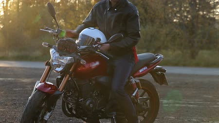 A young man in black leather jacket with white helmet goes to his motorcycle and sits on it before journey at autumn sunset. Close up shot.