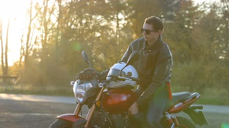A young man in black leather jacket with white helmet goes to his motorcycle, sits on it and shows middle finger in camera before journey at autumn sunset. Close up shot.