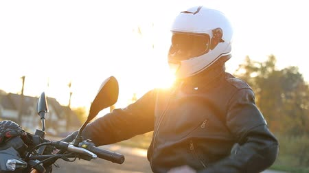 A young man in a black leather jacket sits on a motorcycle. Close up shot. Wideo