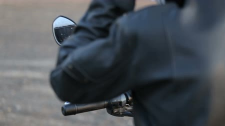 A young man in a black leather jacket sits on a motorcycle. Close up shot. Mirror view. Wideo