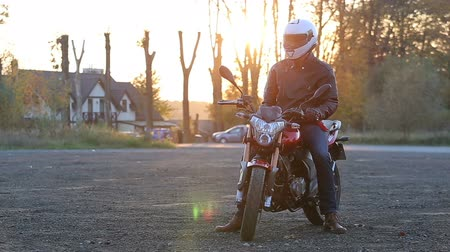 A young man in black leather jacket and white helmet sits on a motorcycle. Wideo