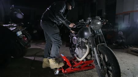 Motorcycle is lifted with hoist by mechanic in workshop..