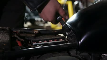 Mechanics hand unscrewes the nut to unlock fuel tank. Close up.