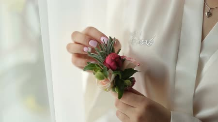Bride holds boutonniere in her hands on wedding preparation. Close up.