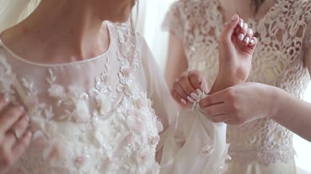 buttoning : The buttons on the wedding dress are fastened by bridesmaid. Morning gathering of the bride. Close up. Stock Footage