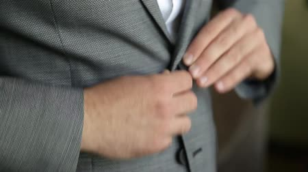 iyi giyimli : Groom is buttoning a jacket. Stylish man in a suit fastening buttons on his jacket preparing to go out. Close up