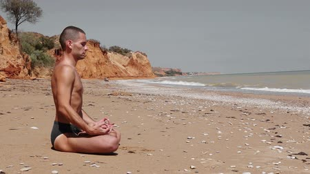 pozisyon : Young man in a Yoga lotus position on the deserted Wild Sea Beach storm before Stok Video