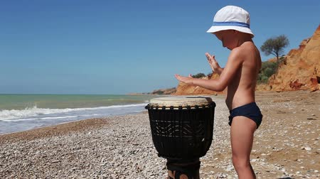davulcu : Little Boy Funny Playing Ethnic African Djembe Drum on the Lonely Wild Beach Stok Video