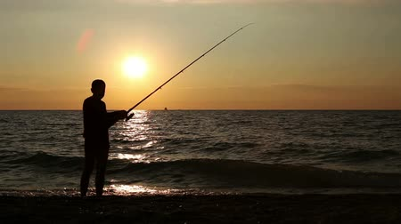 fishermen : Fisherman on the  calm Sunset seaside  Stock Footage